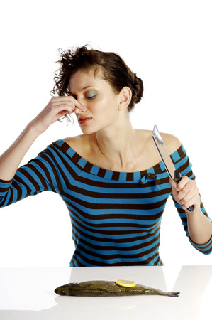 Woman pinching her nose while cutting a fish photo