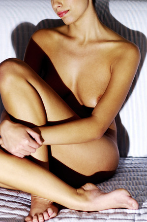 nude young woman: Nude young woman sitting on the couch Stock Photo