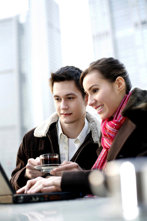 Couple drinking coffee while using laptop in the cafe photo