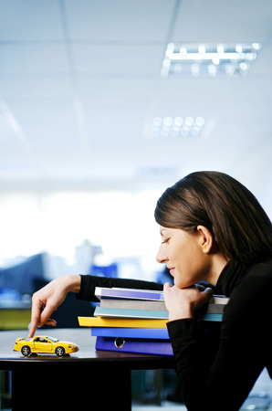 Businesswoman resting her chin on a stack of books while playing with a toy car photo