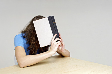 revision book: Woman covering her face with a book Stock Photo