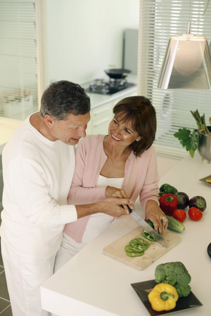 guides: Man guiding woman in cutting vegetable