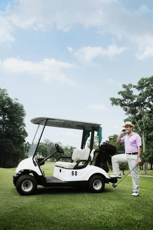 Man talking on the mobile phone by the golf cart photo