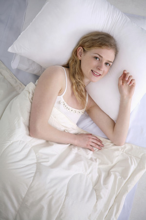 Woman smiling at the camera while lying on the bed photo