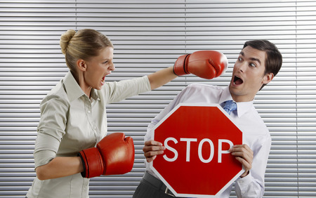 Businessman holding 'Stop' sign, businesswoman punching him photo