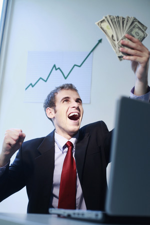 jubilating: Businessman laughing while looking at banknotes