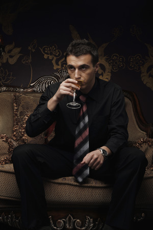 southern european: Businessman drinking a cocktail