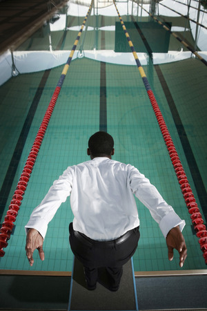 Businessman preparing to dive into the pool photo