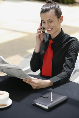 Businesswoman talking on the mobile phone while reading newspaper photo