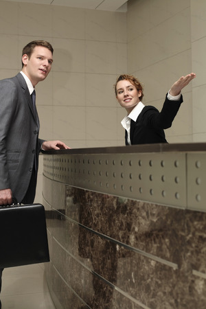 Receptionist showing direction to businessman photo