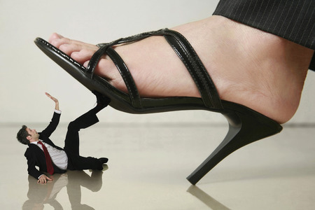 domination: Giant foot stepping on businessman