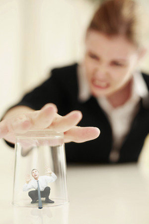 demanding: Businesswoman covering a tiny businessman under a transparent glass