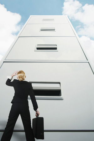 stood up: Businesswoman looking up at a giant cabinet