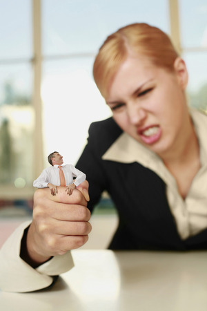 demanding: Businesswoman squeezing a tiny businessman Stock Photo