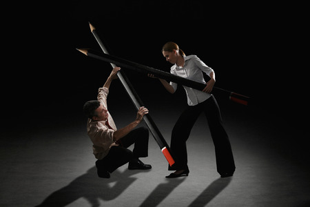 Businessman and businesswoman fighting using giant pencils photo