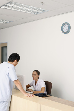Patient talking to nurse at the reception counter photo