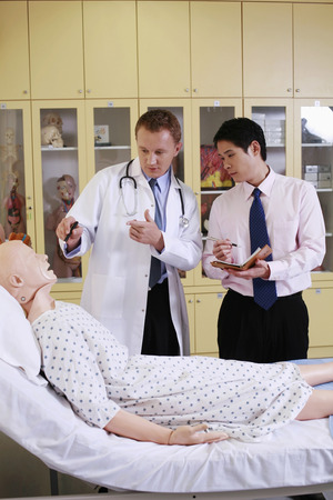 explains: Doctors examining dummy patient on the bed