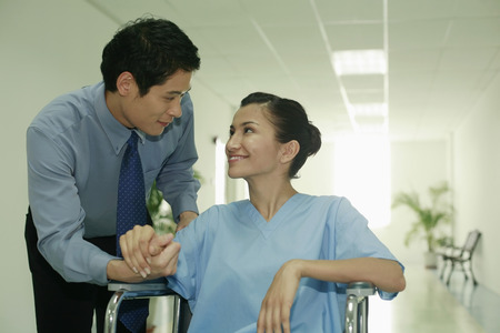 Woman on wheelchair, man holding her hand photo