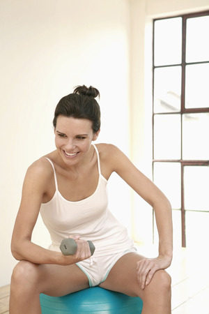 body toning: Woman sitting on fitness ball, lifting dumbbell