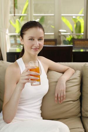 jugo de frutas: Mujer con un vaso de jugo de fruta sentado en el sof� Foto de archivo