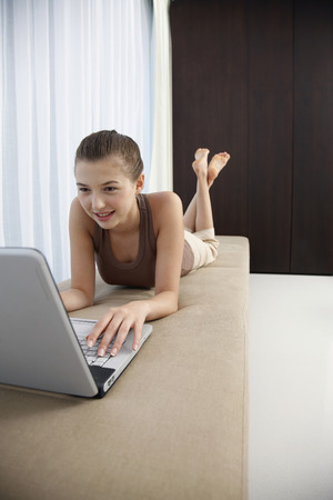 lays forward: Woman lying forward on sofa with legs up, using the laptop Stock Photo