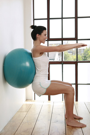 Woman pressing fitness ball against the wall, arms stretching forward photo