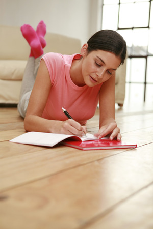 lays forward: Woman lying forward on the floor writing diary