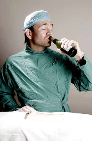 operation gown: Doctor drinking alcohol in operation room
