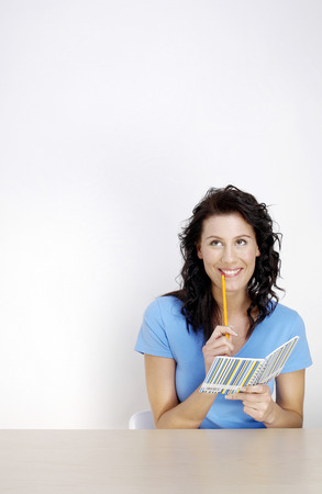 Woman holding a pencil and a note book thinking