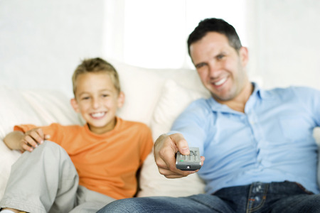 Father and son watching television together photo