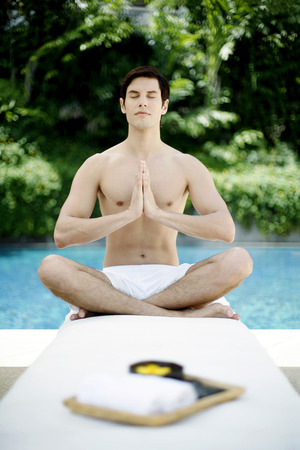bare chested: A guy doing yoga by the poolside Stock Photo