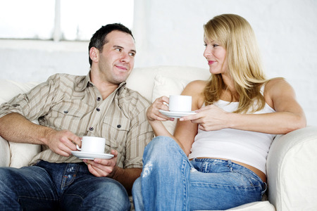 Couple resting on couch enjoying coffee Imagens