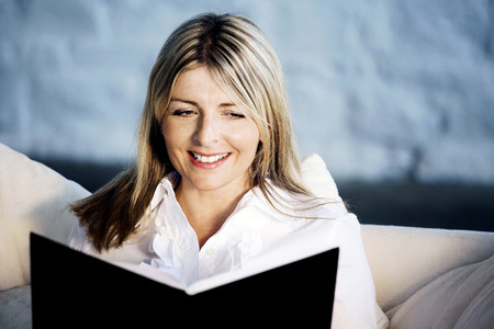 A business lady smiling while reading Imagens