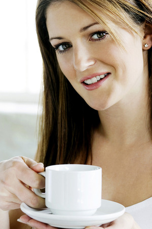 A young lady looking at camera while holding a cup of coffee photo