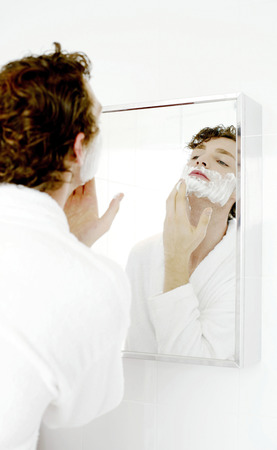 Man applying shaving cream on his face photo