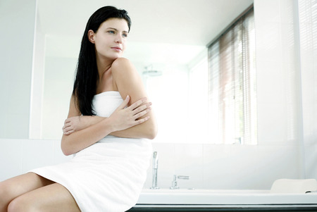 Woman in towel sitting on the bathtub Stock Photo