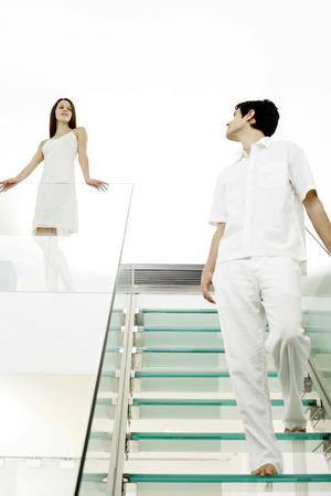 bajando escaleras: Mujer mirando al hombre caminando por la escalera
