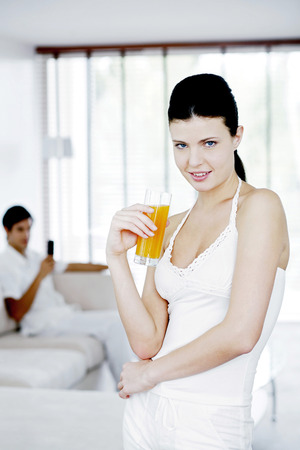 Woman holding a glass of orange juice with her boyfriend sitting in the background photo