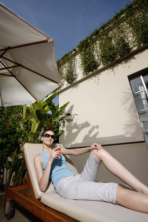 Woman with sunglasses relaxing on lounge chair with a glass of fruit juice photo