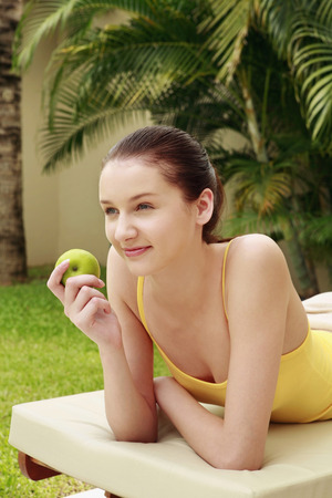 lays forward: Woman lying forward on lounge chair holding green apple Stock Photo