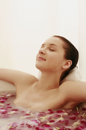 soaking: Woman relaxing in bathtub with flower petals Stock Photo