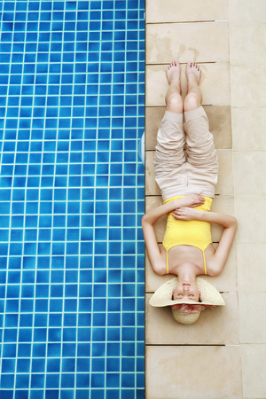 closes eyes: Woman relaxing by the poolside Stock Photo