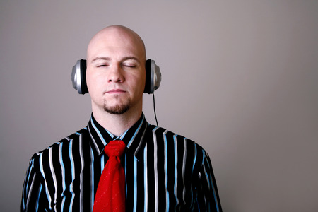Businessman closing his eyes while listening to music on the headphones photo
