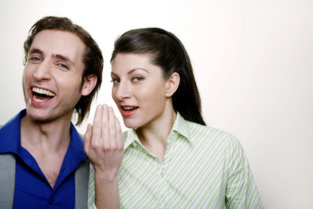 Businesswoman whispering into businessman's ear photo