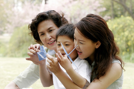 Boy watching his mother making origami Stock Photo - 26231468