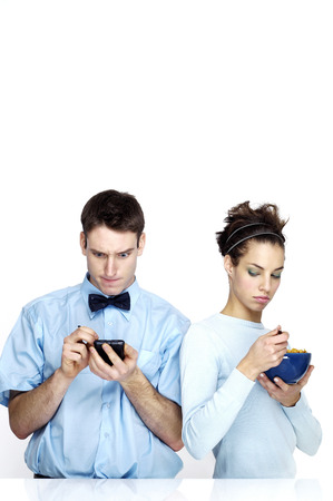 Woman glaring at her boyfriend using palmtop while eating breakfast cereal photo