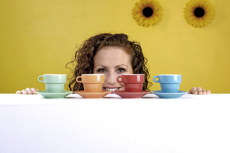 Woman looking at an arrangement of cups and saucers photo
