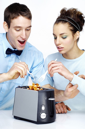 Couple trying to take out waffles from the toaster photo
