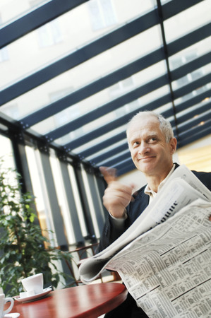 Businessman calling the waiter while holding a newspaper photo