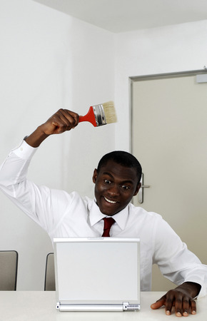 Businessman holding paint brush while using laptop photo